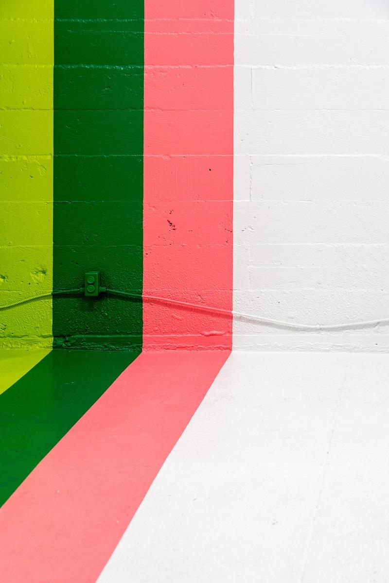 Vägg målad i vitt, rosa, grön och lime