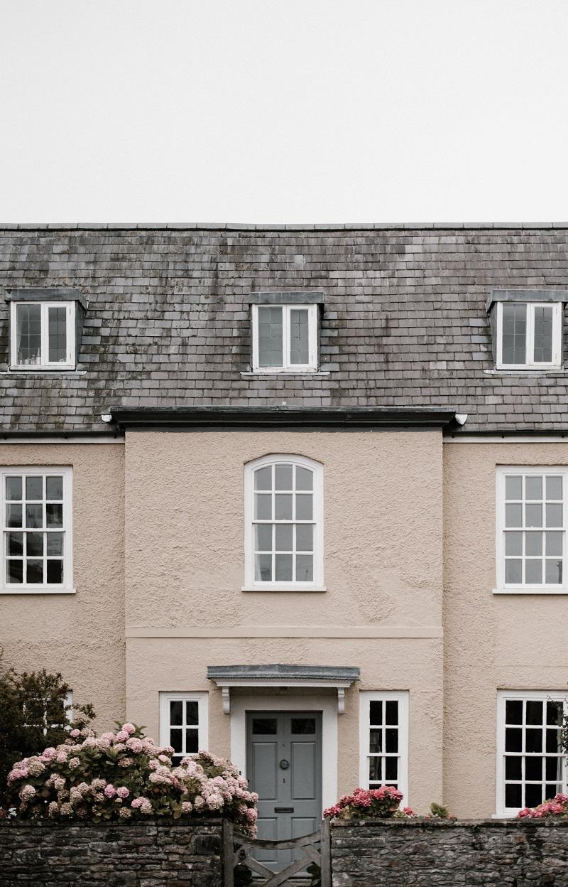 Stort hus med putsad fasad och svarta takpannor.