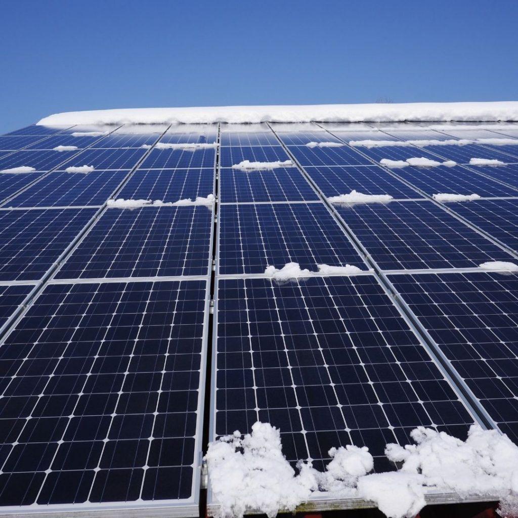 Solceller som har snö på sig